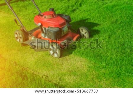 Blurred lawn mower cutting green grass in backyard,Garden service,grass cutter cutting green lawns. #513667759