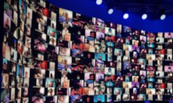 Blurred LED screen of many people faces.Concept : New normal event production.Lots people join online event.Online meeting or seminar. Work at home,video conference,social distancing due to covid-19.