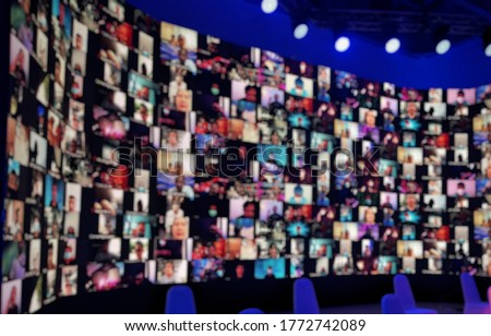 Blurred LED screen of many people faces join big online event or live conference.Work at home.Video online conference.Social distancing reduce risk coronavirus.New normal event production.Online semin