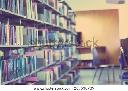 Blurred library with books on the shelf, chairs table and the light from windows in public library. selective focus Blurred effect. Background for your pictures
