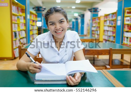 blurred library with books on the shelf, selective focus on thai young woman student in uniform is reading a book
