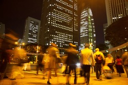 Blurred light motion people walk on street in the city night
