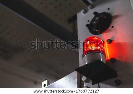 blurred low key Illuminated factory industry red alert emergency light with copy space for background. Attention concept, tragedy, emergency, safety and insurance Stockfoto ©