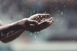 Blurred male hand play catching rain drops on blurred grey background. Pure rainy spring weather joy under waterfall splash, rain season