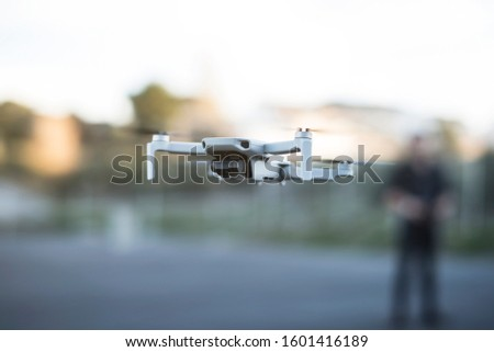 Blurred Man controlling drone in outdoors image with remote control and smartphone