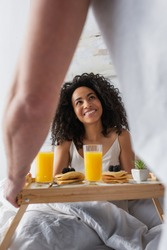 blurred man holding tray with breakfast and glasses of orange juice near happy african american girlfriend