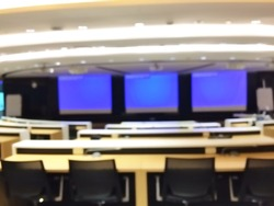 Blurred meeting room interior with blue monitor screen
