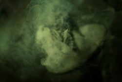Blurred, mint green, wisp of smoke from burning incense. Fuzzy looking soft background texture image.