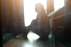 Blurred model, Asian woman sit on the floor beside window in dark room, place hand on knees. Seem that people are suffering, unhappy, broken heart or experience life problems. Taken pass dirty mirror