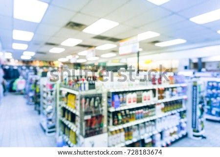 Blurred modern convenience store gas station in Arkansas, USA. Variety items on display such as impulse snack, energy drink, coffee, hot food, tobacco, cigarette, clothes, lottery ticket. Vintage tone #728183674