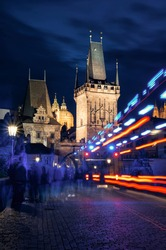 Blurred motion blure light traces and ghost like people silhouettes walking on illuminated Charles Bridge in Prague in night on Gothic towers background