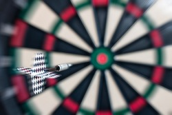 Blurred motion image of a dart flying towards the bull's eye of a target. Playing concept