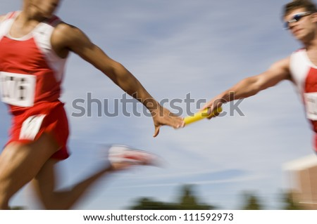 Stock Photo Blurred motion male runners passing baton in relay race