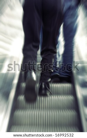 Blurred motion of business commuters on escalator