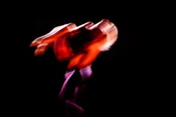 Blurred motion of dancers in contemporary dance performance with dark background