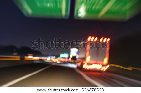 Blurred motion of defocused semi truck speeding on highway under street signs - Night traffic and transport logistic concept with semitruck container driving on speedway - Tilted and bokeh composition