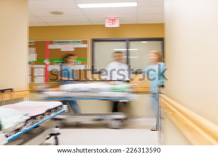 Blurred motion of doctor and nurses with stretcher in hospital corridor