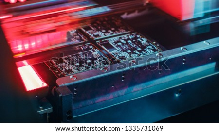 Blurred motion of Factory Machine at Work: Printed Circuit Board Being Assembled with Automated Robotic Arm, Surface Mounted Technology Connecting Microchips to the Motherboard. Macro Close-up . #1335731069