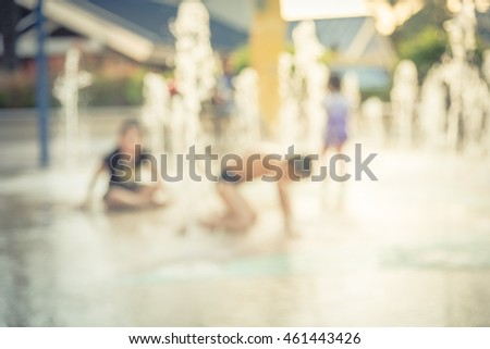 Blurred motion of kids having fun play with water at playground in summer time. Activities for children and family at urban outdoor aquatic park with water sprinkles and fountain. Vintage filter look. - Shutterstock ID 461443426