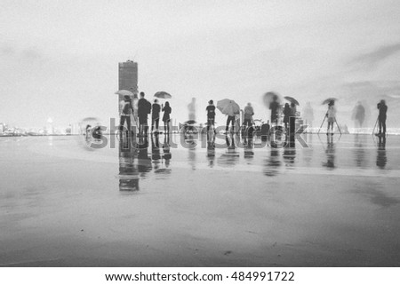 Blurred motion of people taking picture under the rain in black and white, grain texture style