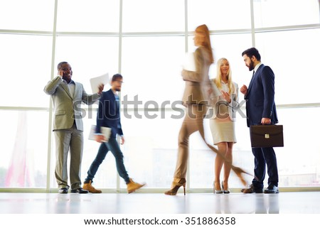 Blurred motion of several people working at office