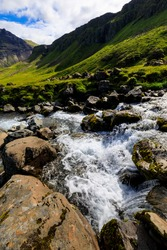 Blurred motion of water flowing over rapids in the fast flowing Grundara River, with a backdrop of green mountain cliffs, Summer, Grundarfjordur,  Snaefellsnes Peninsula, West Iceland, Europe