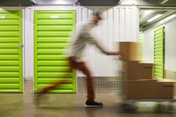 Blurred motion shot of unrecognizable man pushing cart with boxes while running in self storage facility, copy space