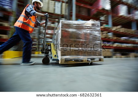 Blurred motion shot of warehouse worker wearing hardhat and reflective jacket pushing moving cart with boxes along isle between tall racks #682632361