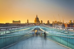 Blurred motion view over the Millennium footbridge looking towards St. Paul's Cathedral at sunset