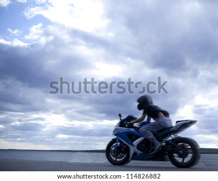 blurred motorcyclist against blue sunset