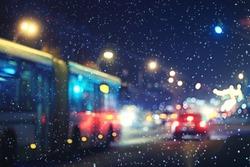 blurred night background city traffic road city lights winter snow glare