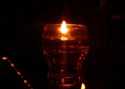 blurred night view light  floating candle wick on glass of oil