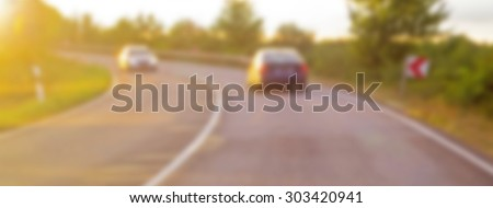 Blurred noise  image of two cars on the road turn.