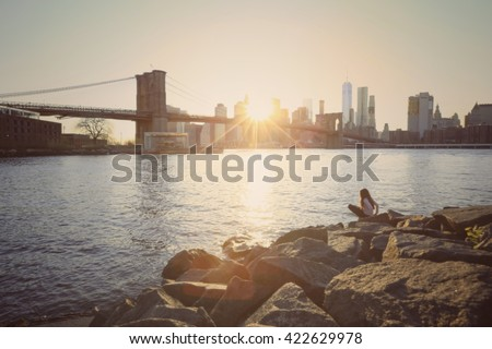 Stock Photo Blurred of a girl sitting on rocks with the view of Brooklyn Bridge and Manhattan skyline at sunset in vintage colour