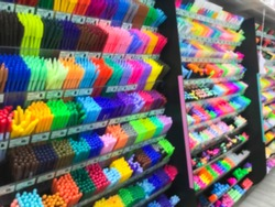 Blurred of stationery shop with many accessories such as pen, pencil, eraser, color, correction pen, highlighting pen, ink and etc. Side view of School supplies on shelf for students