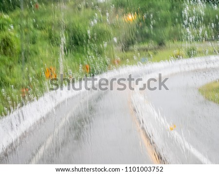 Blurred of wetting glass in front of a moving car on slipping curve road or street in rainy day can use for warning photo to be careful when driving the vehicle in raining season. #1101003752