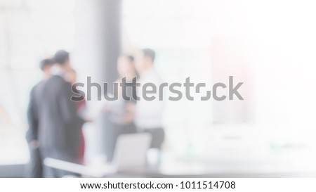 Blurred office interior space with businessman and businesswoman meeting background with copy space.