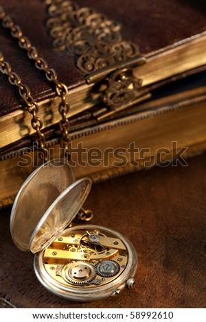 Blurred old books on the background of an antique pocket watch