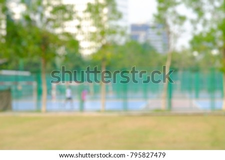 Blurred outdoor soccer court at the park in the city with green fence and trees view,bokeh light and high buildingss