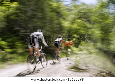 Blurred panning shot of three mountain bikers riding through the forest.