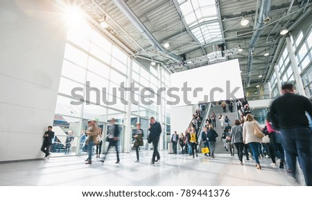 blurred people at a trade show, including copy space banner