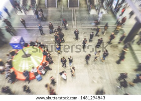 Blurred people crowd inside train station rushing at busy hour - Concept of modern, urban, city life, business, shopping - Focus on center person with blue jacket - Defocused radial effect #1481294843