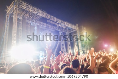 Blurred people dancing and having fun in summer festival party outdoor - Crowd with hands up celebrating fest concert event - Defocused image - Youth,fest,event,music, and entertainment concept