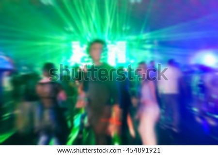 Blurred People dancing with original laser green lights in background - Defocused image of new generation disco club - Concept of nightlife with music - Blurry background