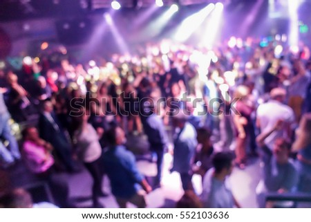 Blurred people dancing with original laser pink lights  - View of new generation disco club - Defocused image - Concept of nightlife with music entertainment - Warm filter