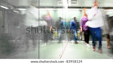 Blurred people in a hurry reflected in mirror