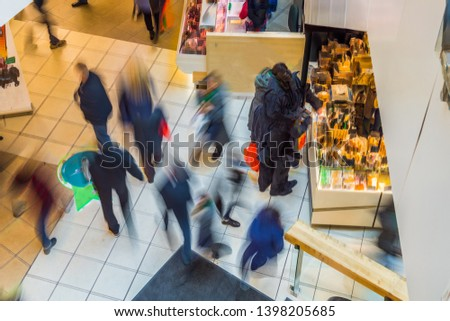 Blurred people in motion blur, rushing in the lobby of shopping mall. View from above. #1398205685