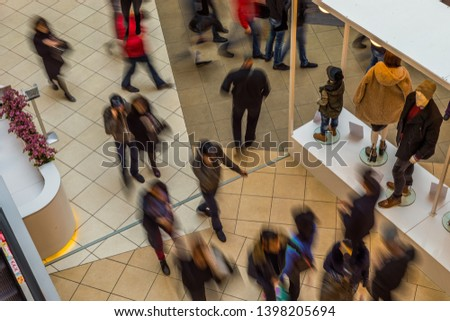 Blurred people in motion blur, rushing in the lobby of shopping mall. View from above. #1398205694