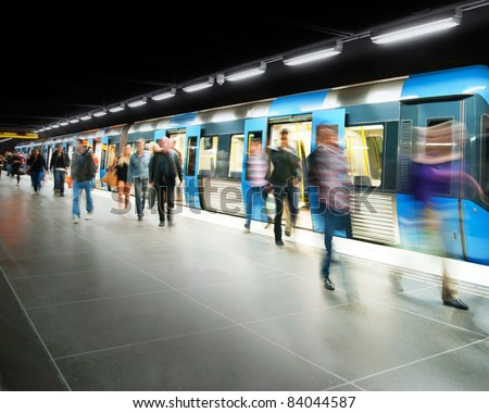 Blurred people on subway platform leaving the train