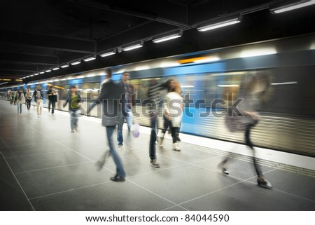 Blurred people on subway platform with moving blue train - stock photo